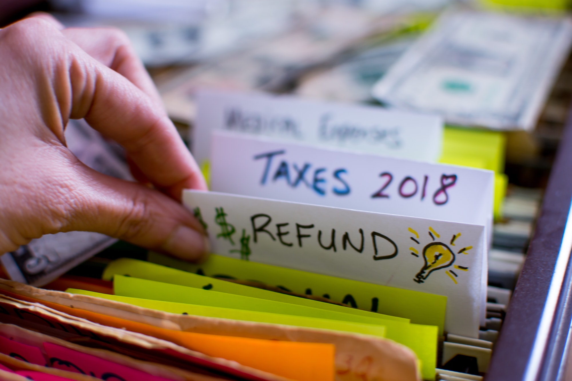 Tax files and tax refund files in a filing cabinet with woman going through tax records