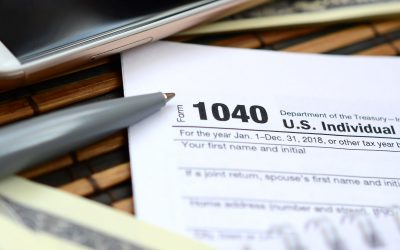 The pen, notebook, smartphone and dollar bills is lies on the tax form 1040 U